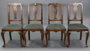 A set of four Queen Anne-style dining chairs with shaped splat back, padded seats, & on slender