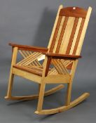 A Tamarack maple & cherry wood rocking chair with slatted seat & back, & on square supports.