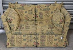 A Knole-style two-seater settee, upholstered cream material & with all-over repeating