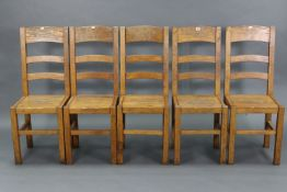 A set of five light oak rail-back dining chairs with hard seats, & on square legs with plain