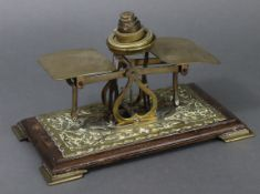 A late Victorian brass embossed letter scale mounted on an oak platform base, & with five brass