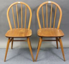 A pair of Ercol spindle-back kitchen chairs with hard seats, & on round tapered legs with spindle