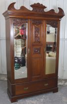 A Victorian walnut wardrobe with carved & shaped cornice with carved centre panel flanked by
