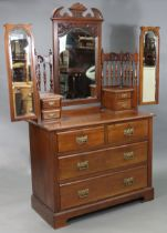 A Victorian walnut dressing chest with three mirrors to the stage back, fitted two short & two
