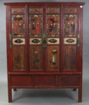 A Chinese red lacquered pine tall side cabinet with fitted interior enclosed by two pairs of