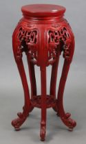A Chinese-style red lacquered wooden jardinière stand with circular top, with pierced frieze, & on