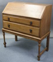 An early/mid-20th century oak bureau with fitted interior enclosed by fall-front above two long