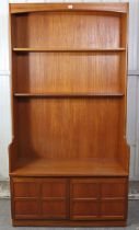 A Nathan teak tall wall unit fitted two shelves above cupboard enclosed by a pair of panel doors,