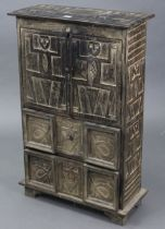 A Peruvian-style ebonised wooden small upright cabinet with all-over carved figure-scene decoration,