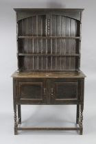 A 1930's small oak dresser the upper part fitted two open shelves & with panelled back, the cupboard