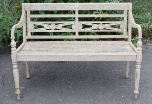 """A teak slatted garden bench with shaped open arms, & on turned front legs, 47¼"""" long."""