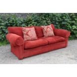 A modern three-seater settee with scroll-arms, & with loose cushions to the seat & back