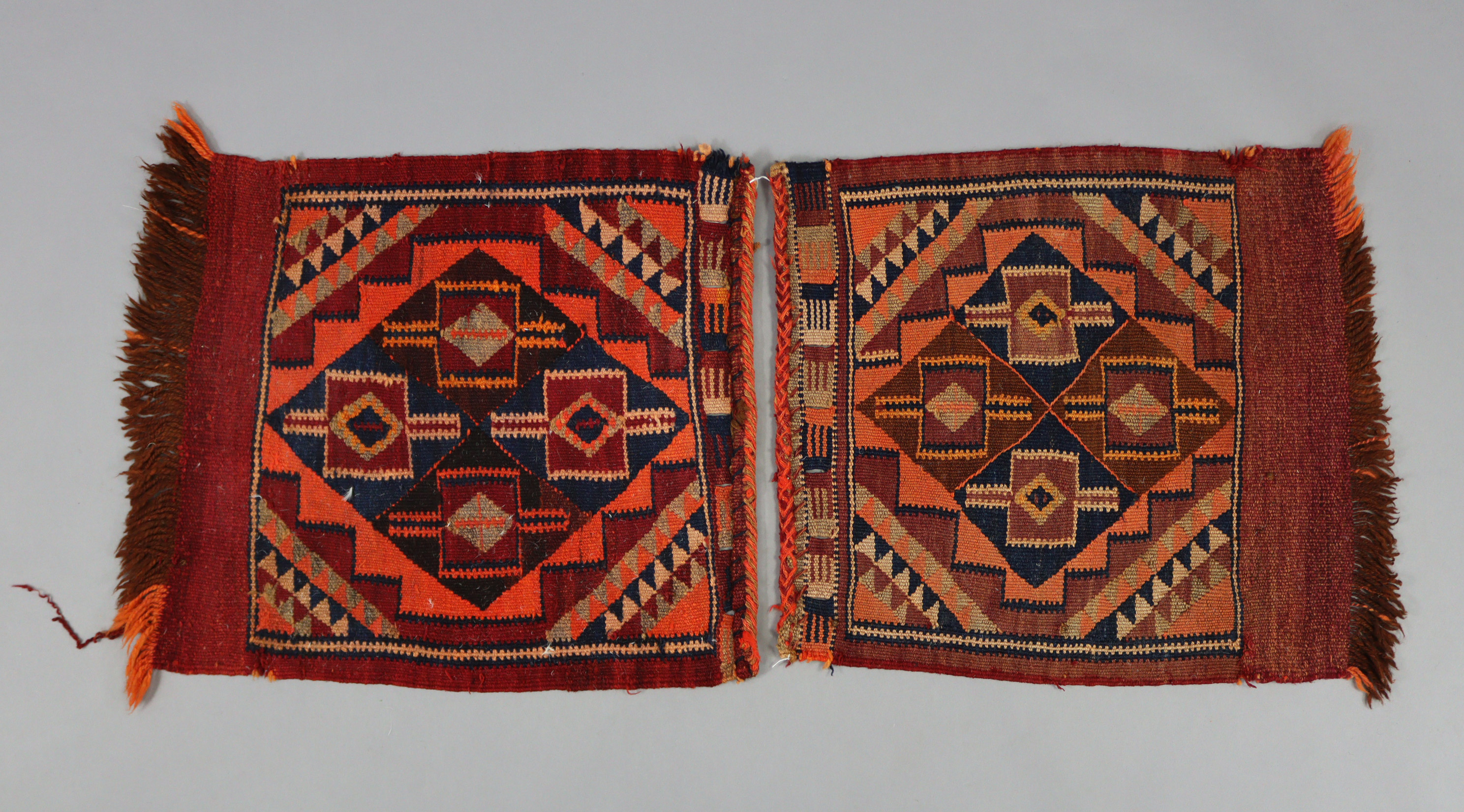 A pair of Afghan small rugs or saddlebag faces, each of madder ground with repeating lozenge &