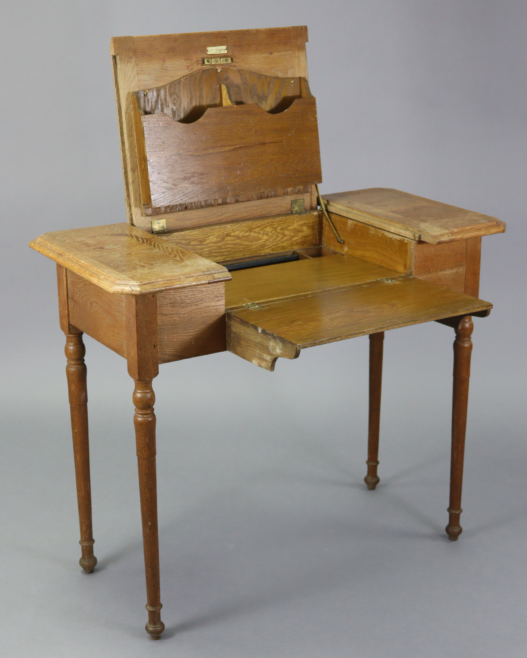 An Edwardian oak writing table with fitted interior enclosed by three hinged panels, & on turned