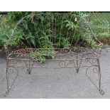 A Victorian-style wrought-iron two-seater garden bench with pierced scroll decoration, & on shaped