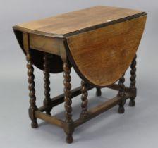 A 1930's oak oval gate-leg dining table on barley-twist legs & turned feet with plain stretchers,