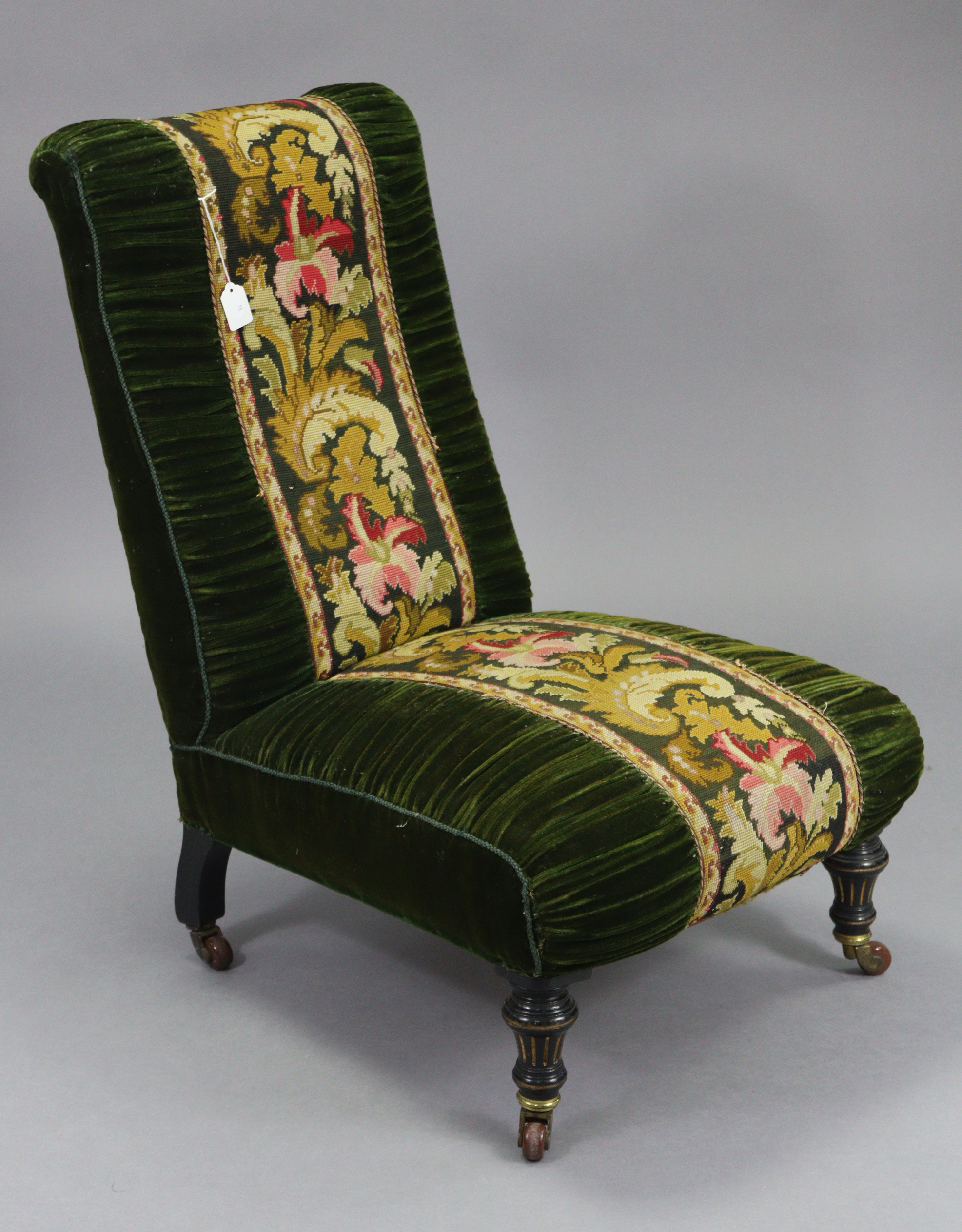 A late 19th century nursing chair upholstered green velour & multi-coloured foliate embroidery, on