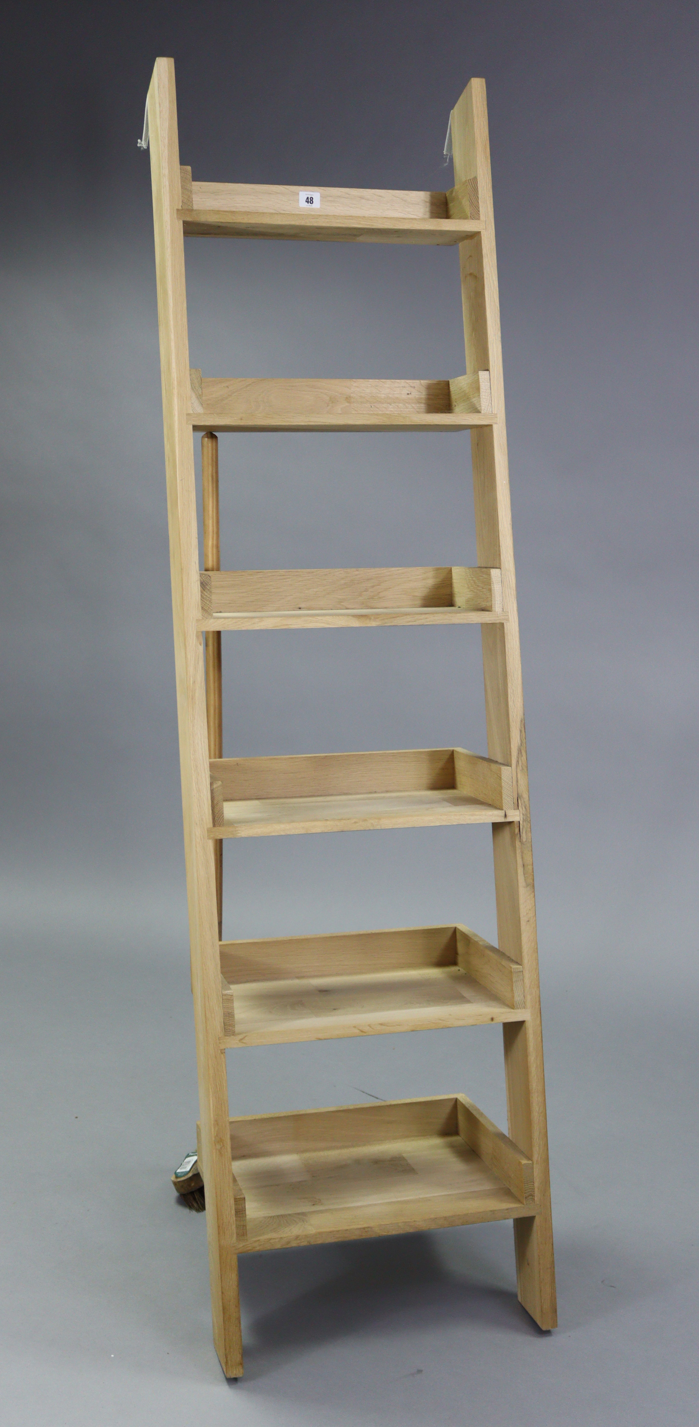 "A light oak tall six-tier lean-to shelf unit, 18¾"" wide x 71"" high."