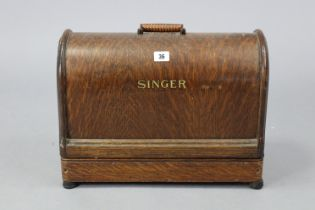 A singer hand sewing machine with oak carrying case.
