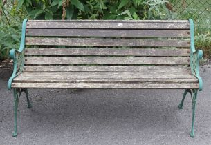 """A teak slatted garden bench on green painted cast-iron end supports, 50"""" long."""