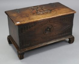 A small oak coffer with carved decoration to the hinged lift-lid & front, & on carved bracket