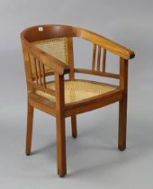 A teak tub-shaped chair inset woven-cane panel to the seat & back, & on square tapered legs.