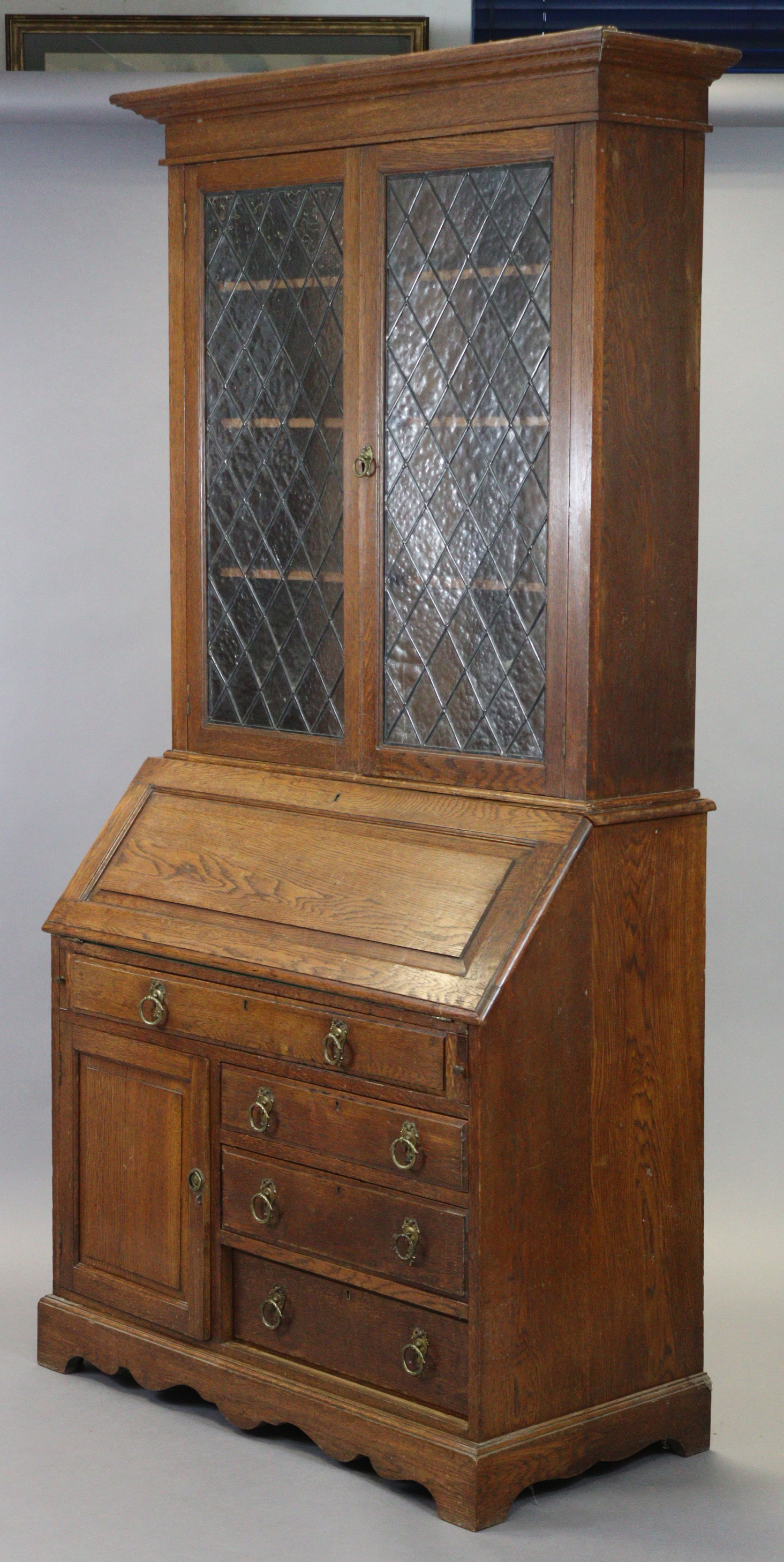 A late 19th/early 20th century oak bureau-bookcase with moulded cornice above a pair of leaded