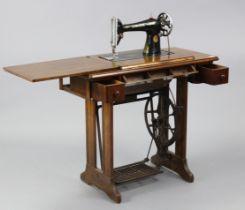 "A Singer treadle sewing machine in walnut case, 34"" wide x 30½"" high."