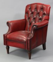 A red leather buttoned-back armchair on short turned legs.
