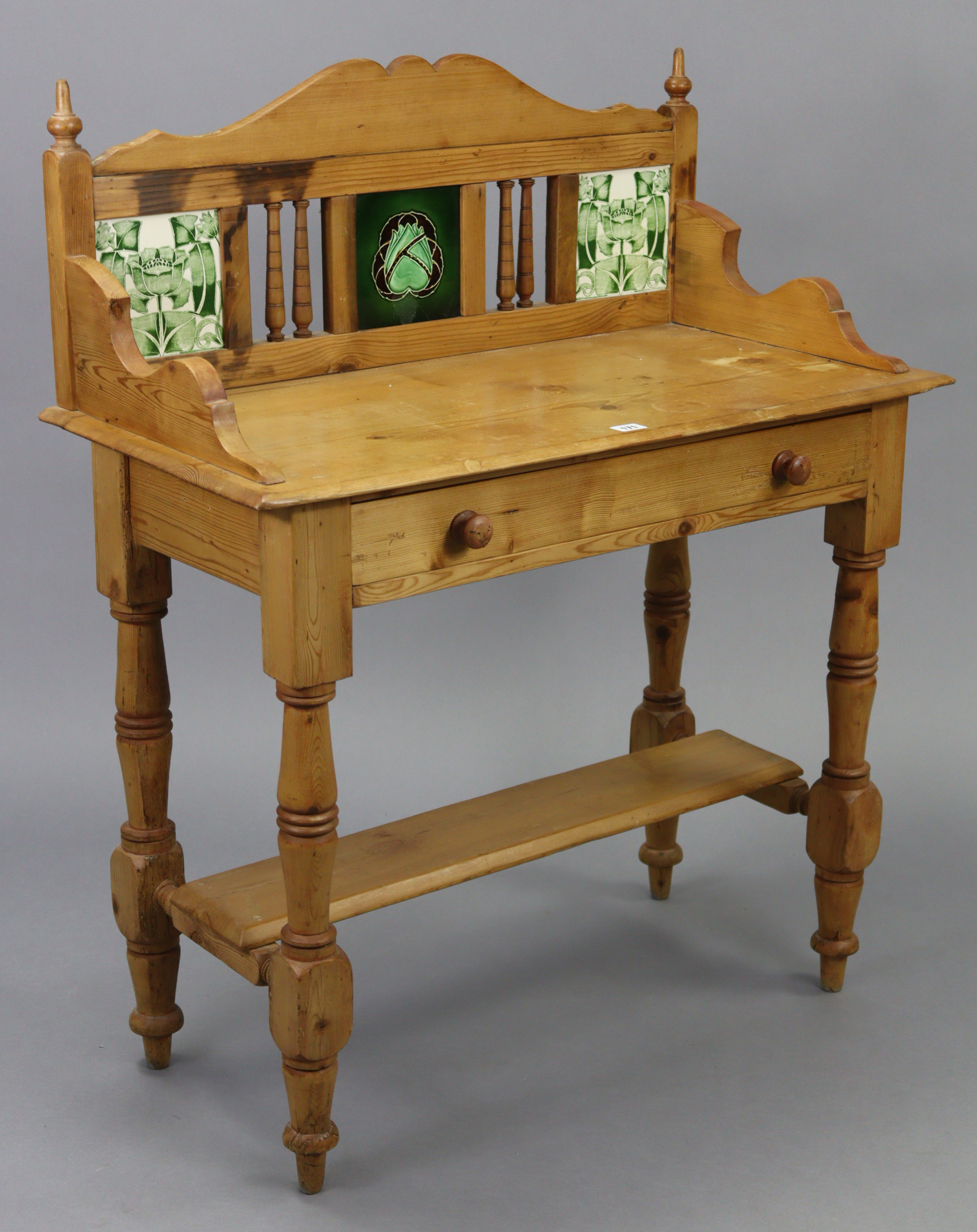 A pine washstand, inset tiles to the stage back, fitted frieze drawer, & on turned legs with open