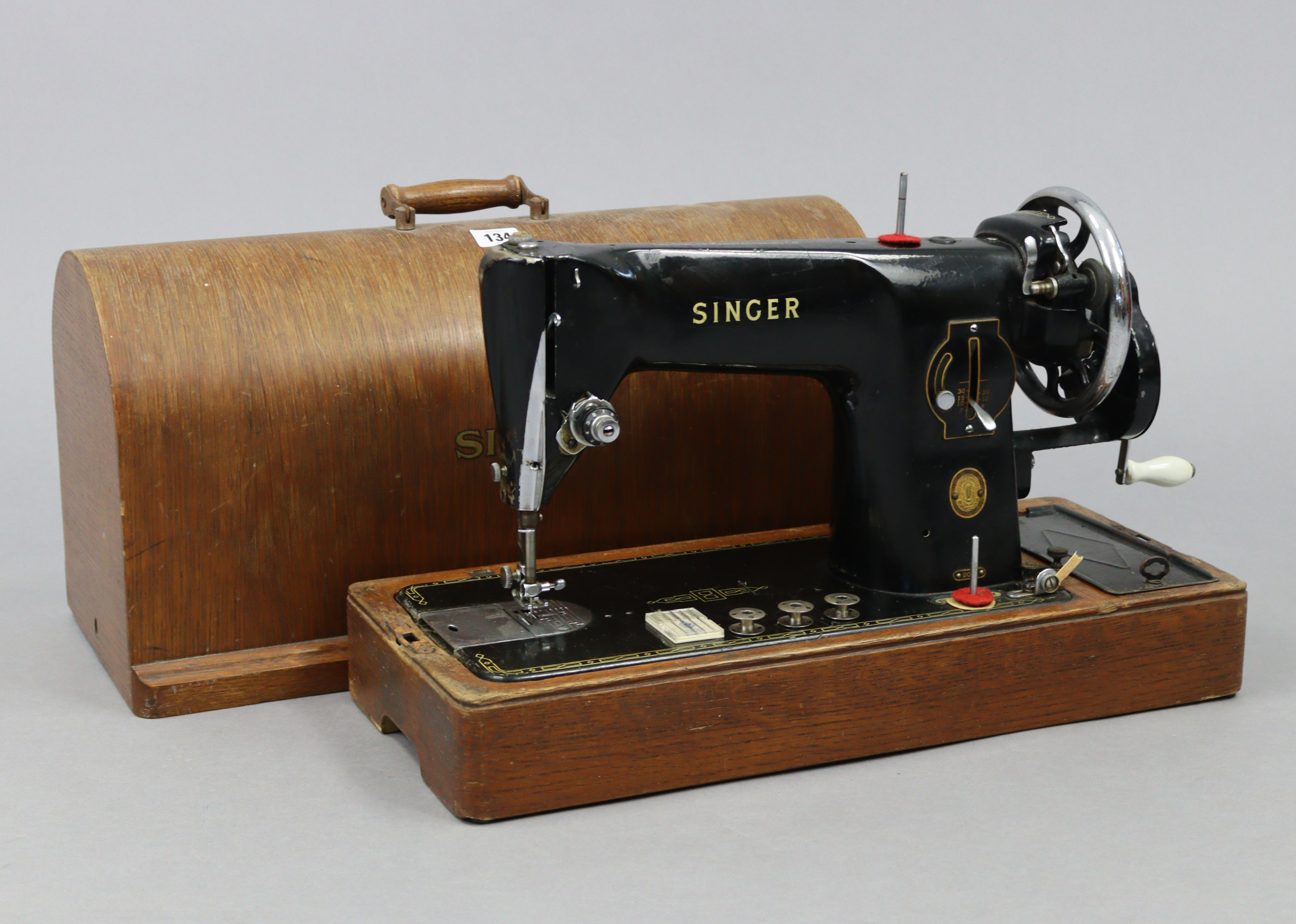 A Singer hand sewing machine with oak case.