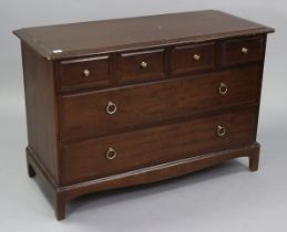 """A Stag """"Minstrel"""" mahogany-finish low chest fitted three short & two long drawers, & on shaped"""