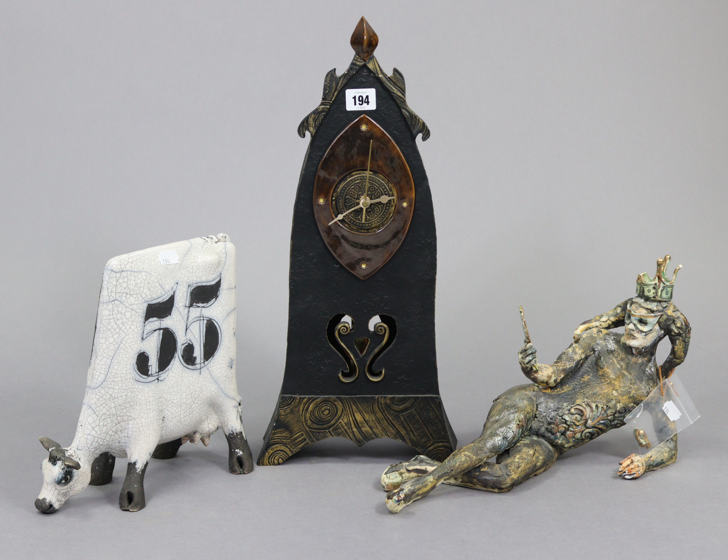 """A mantel clock in black glazed pottery case, 19¼"""" high; a contemporary pottery model of a cow,"""