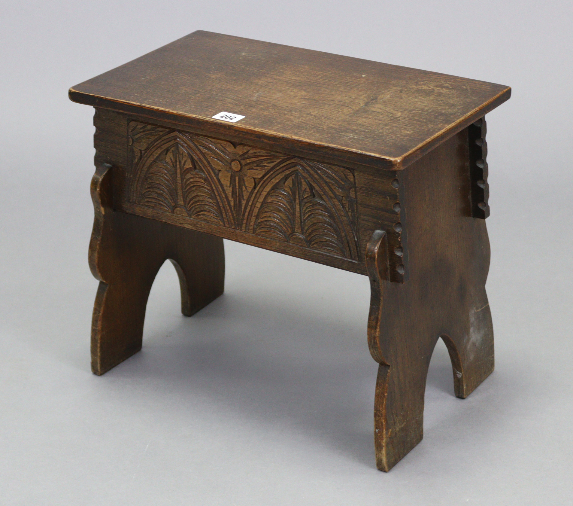"""An oak box-seat stool with hinged lift-lid, carved front & with shaped end supports, 17¼"""" wide x 15"""""""