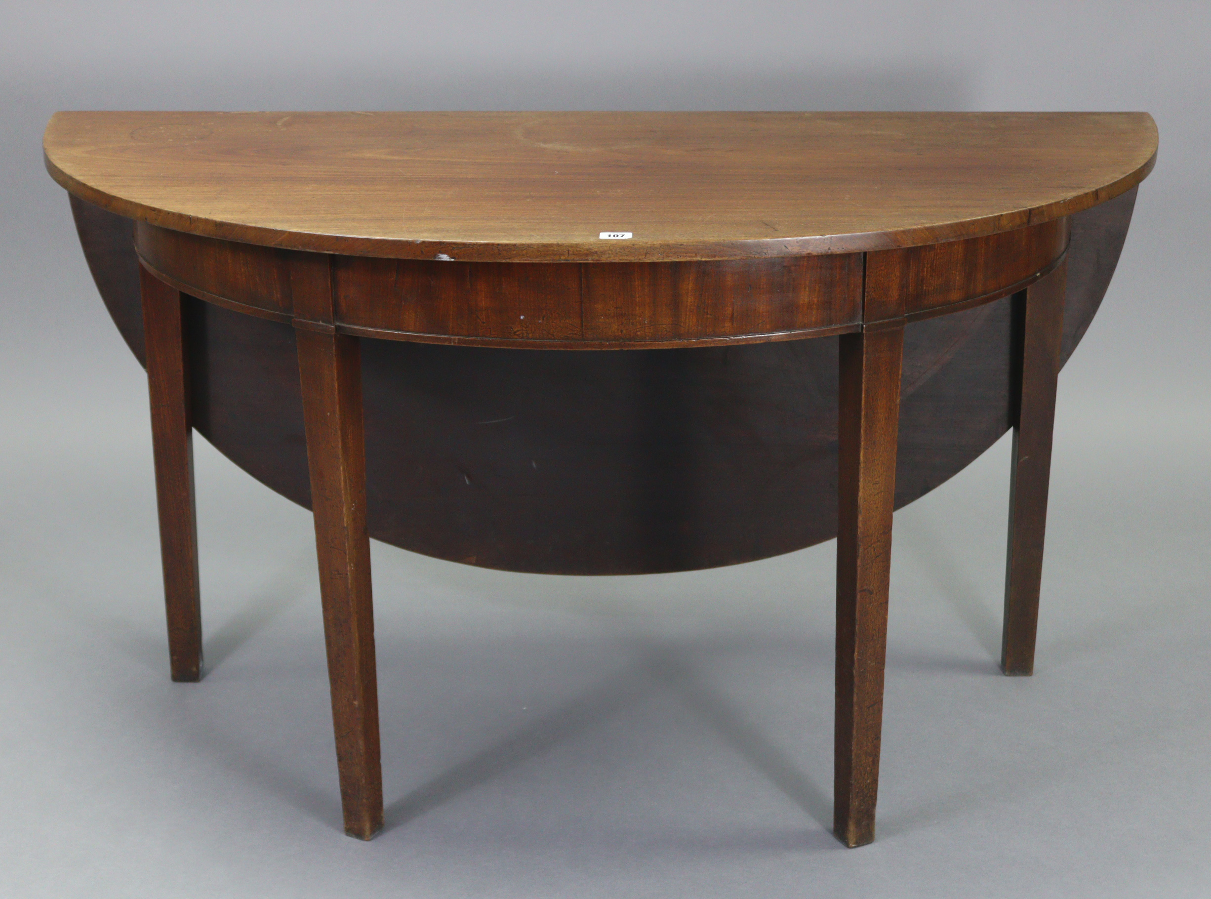 An early 20th century mahogany circular single-drop leaf dining table on four square tapered legs,