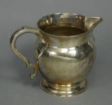 A George V silver round bulbous jug in the 18th century style, with short flared neck, scroll