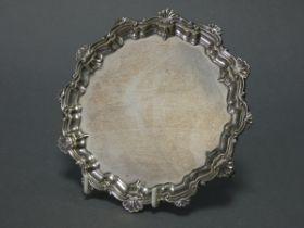 """An Edwardian silver card tray with raised pie-crust & shell border, & on three scroll feet, 6"""""""