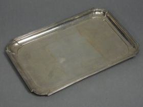 A George V silver rectangular dressing table tray with raised border, reeded rim, & rounded corners,
