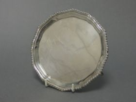 """A silver card tray with raised shaped border & gadrooned rim, on four pad feet, 6¼"""" diam., Chester"""