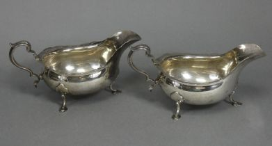 A pair of Georgian-style silver sauce boats with card-cut rims & scroll handles, each on three splay