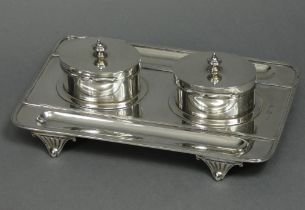 An Edwardian silver desk inkstand of rectangular form with reeded rims, a pen-trough either side,