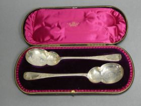 A pair of late Victorian silver serving spoons with gourd-shaped bowls & all-over engraved