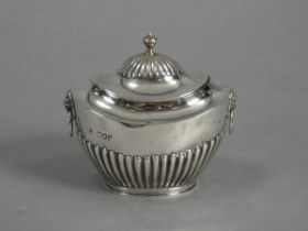 A late Victorian silver tea caddy of oval semi-fluted form, with hinged lid & lion-mask ring