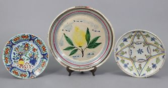 """A 19th century French faience shallow bowl with painted floral decoration 12¾"""" diam.; a similar"""