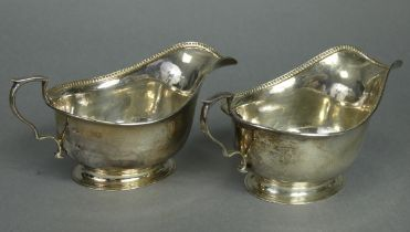 """A pair of George V silver sauce boats with egg-&-dart rims, each on oval spread foot, 6¾"""" long;"""