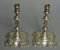 A pair of cast silver tapersticks in the mid-18th century style, with reel-shaped nozzles, slender