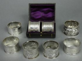 A pair of Victorian silver napkin rings with beaded rims & engraved flower-head & star decoration,