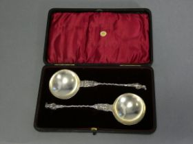 A pair of late Victorian silver apostle serving spoons, both depicting St. Peter, with writhen stems