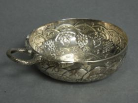 A French silver wine taster with serpent handle, the round bowl embossed with grapevines & inset