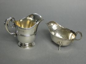 """A Victorian silver helmet-shaped milk jug with scroll handle, & on round pedestal foot, 4"""" high,"""
